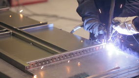 Two welders working, welding metal pieces together at a industrial factory. stock footage