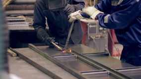 Two welders working, welding metal pieces together at a industrial factory. stock video footage