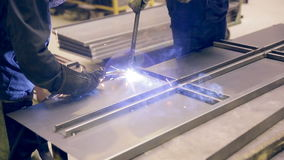 Two welders working, welding metal pieces together at a industrial factory. stock video