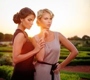 Two well-dressed woman in beautiful park. royalty free stock photo