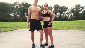 Two well-trained man and woman are posing. Muscular good looking couple posing outdoor, in the morning, somewhere in austria