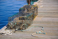 Two well used lobster pots sitting on a dock Stock Images