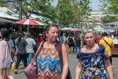 Two westerner mature ladies seem to be friend walking and talking together in Chatuchak weekend market royalty free stock images