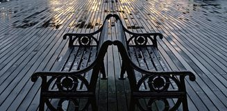 Two Wet Benches On Cromer Pier. Royalty Free Stock Image