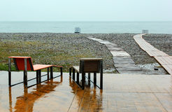 Two wet chairs on empty beach at rainy day in Batumi, Georgia Stock Photo