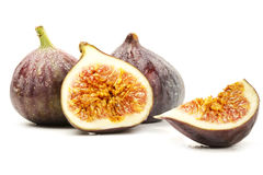 Two wet figs and a half and a fig wedge. On white background Royalty Free Stock Photo