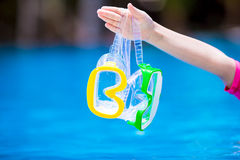 Two wet scuba masks in kid hand near swimming pool Royalty Free Stock Photography