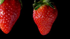 Two wet strawberries collide with each other. Slow-motion drop in extreme close-up stock footage
