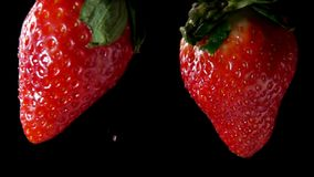 Two wet strawberries collide with each other. Slow-motion drop in extreme close-up stock video footage