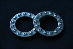 Two Wheel Ball Bearings. Close up of two wheel ball bearings on dark felt background royalty free stock photos