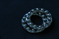 Two Wheel Ball Bearings. Close up of two shiny wheel ball bearings on dark felt background stock photo