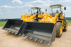 Two wheel loaders excavators. Two Loaders excavators construction machinery equipment outdoors Stock Photos