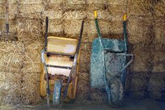 Two wheelbarrows on the hay background stock images