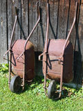 Two wheelbarrows at wooden barn Royalty Free Stock Photos