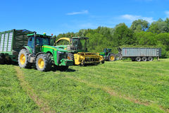 Two-wheeled tractors John Deere trailers with cut grass and forage harvester John Deere Stock Image