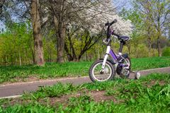 Two-wheeled white-purple bike with extra side wheels stock photo