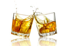 Two whiskey glasses clinking together, isolated Royalty Free Stock Photo