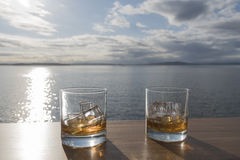 Two Whiskey on rocks to the sun. Two whiskey on rocks glasses on seaside deck with setting sun royalty free stock photos