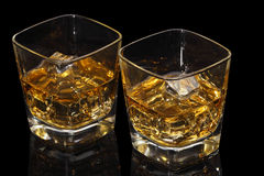 Two whisky glass. Two whiski glass with ice cubes on the black table Stock Image