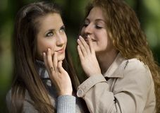 Two whispering girlfriends. On street Royalty Free Stock Images