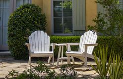 Two white adirondack chairs sitting on a patio in front of windows with green shutters and a hedge with plants around them royalty free stock photos