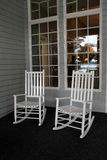 Two white Adirondack rocking chairs on front porch. Two high back Adirondack rocking chairs set close together on front porch, in front of tall windows Royalty Free Stock Image