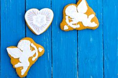 Two white angels and a heart. Ginger biscuits in chocolate glaze. Valentine`s Day. Flat lay. Two white angels and a heart. Ginger biscuits in chocolate glaze Stock Photo