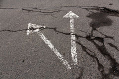 Two white arrows on cracked asphalt texture. Royalty Free Stock Photography