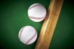 Two White Baseball ball and wooden bat isolated on green felt ba royalty free stock photography