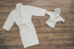 Two white bathrobes on wooden background Royalty Free Stock Image