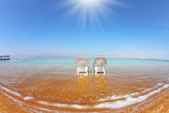 Two white beach armchairs  in the water Stock Images