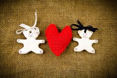 Two white bears with red handmade heart on the sacking backgroun Stock Images