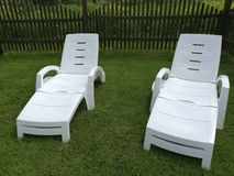 Two white sunbeds for relaxing on the green lawn royalty free stock photography
