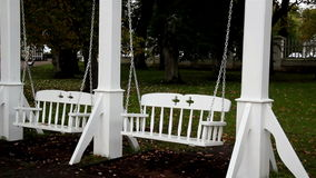 Two white bench swing stock footage