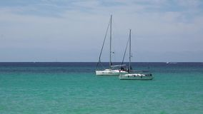 Two white boats floating on turquoise sea water. UHD 4K stock video footage