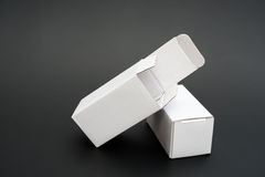 Two white boxed. With one opened and one closed on black royalty free stock photography