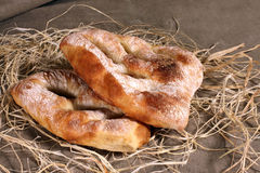 Two white bread lying in straw on grey linen tablecloth Stock Photography
