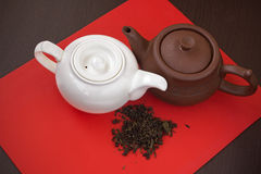 Two white and brown ceramic teapots. Two white and brown ceramic teapots on red board. Teapots and green tea on red and wood background. Сomparing white and Royalty Free Stock Photography