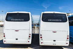 Two white buses parked at the port Stock Photography
