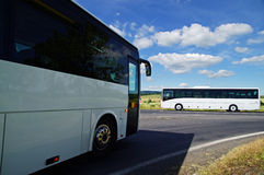 Two white buses passing through the intersection in a rural landscape Stock Photos