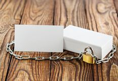 Two white business cards, lock, chain on wooden background . Protection of business and finance. Protection of personal informatio royalty free stock images