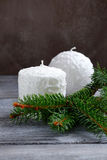 Two white candles on the boards with pine branch Royalty Free Stock Image