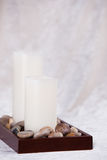 Two White Candles in Polished Rocks Royalty Free Stock Images