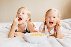 Two white Caucasian children girls eating corn puffs stock photos