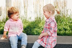 Two white Caucasian cute adorable funny children toddlers sitting together. Group portrait of two white Caucasian cute adorable funny children toddlers sitting stock photos