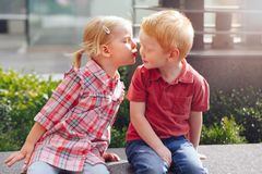 Two white Caucasian cute adorable funny children toddlers sitting together kissing each other. Group portrait of two white Caucasian cute adorable funny children stock photography