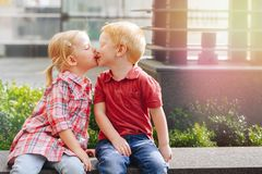Two white Caucasian cute adorable funny children toddlers sitting together kissing each other. Group portrait of two white Caucasian cute adorable funny children Royalty Free Stock Images