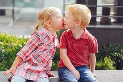 Two white Caucasian cute adorable funny children toddlers sitting together kissing each other. Group portrait of two white Caucasian cute adorable funny children Stock Images