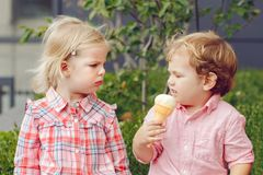 Two white Caucasian cute adorable funny children toddlers sitting together sharing ice-cream food. Group portrait of two white Caucasian cute adorable funny Royalty Free Stock Images
