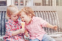 Two white Caucasian cute adorable funny children toddlers sitting together sharing ice-cream food. royalty free stock images